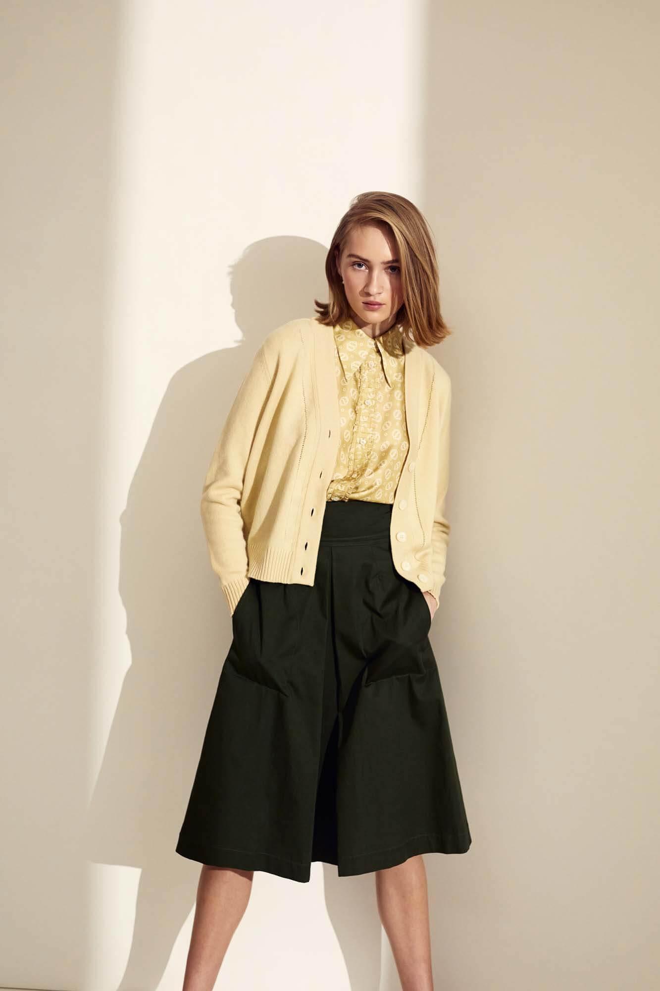 Kvinde som står med gul trøje og grøn nederdel | SS21