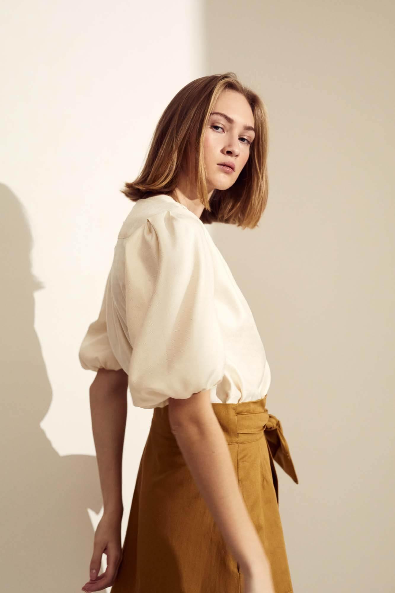 Kvinde med siden til i hvid trøje | SS21