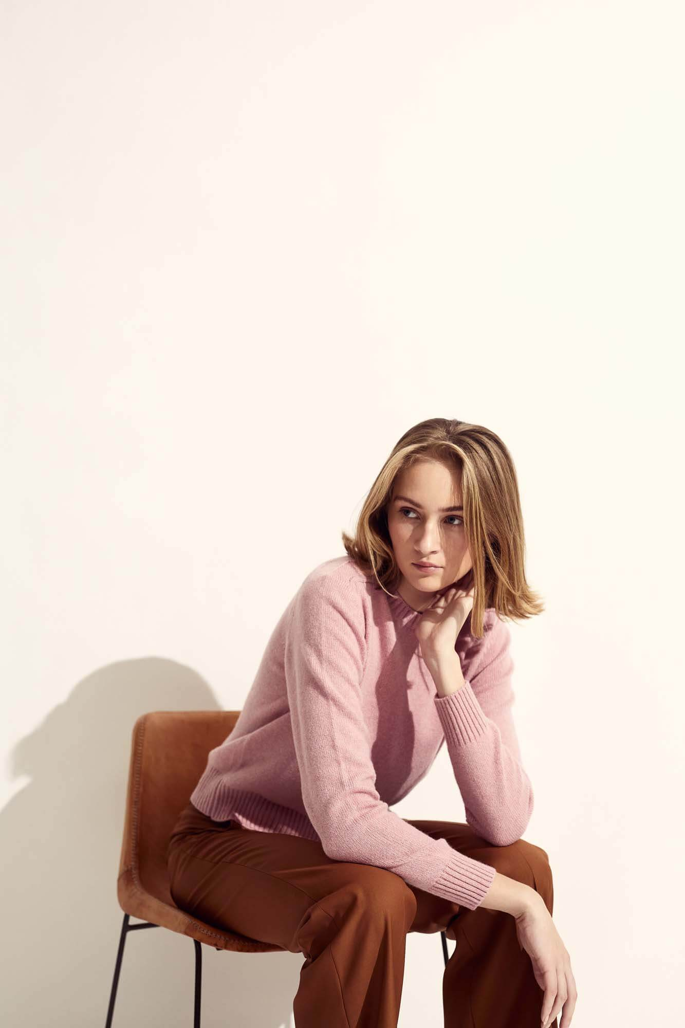 Dame med lyserød strik på stol | SS21